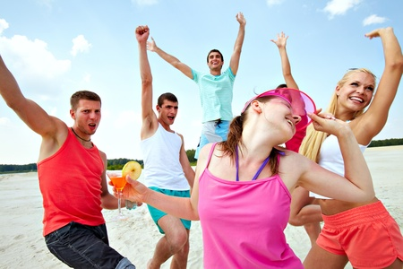 male friends: Six joyful friends dancing on beach during vacation