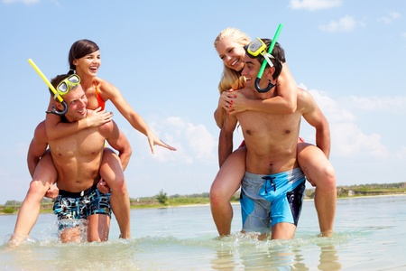 Portrait of happy guys carrying their girlfriends while walking in water  photo