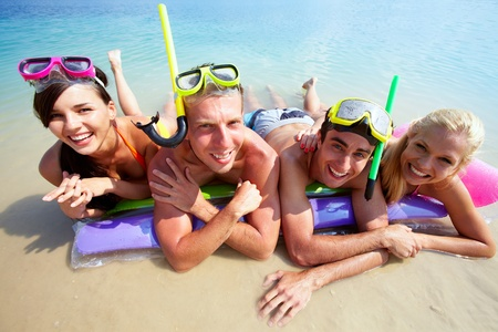 Four friends in scubas lying on sand by water photo