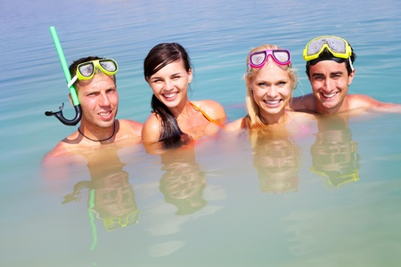 Portrait of two happy couples in water on summer vacation photo