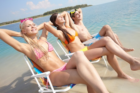 Portrait of three friends resting in chairs on the beach photo