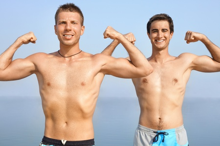mascular: Two happy guys showing their muscles Stock Photo