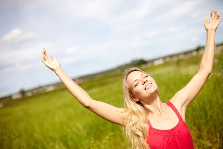 surrender: Image of happy female with raised arms enjoying summer day Stock Photo