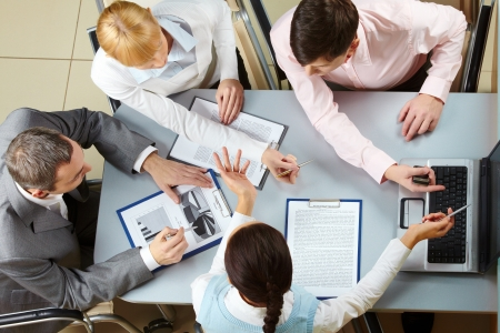 meeting place: Above view of four business partners interacting at meeting Stock Photo