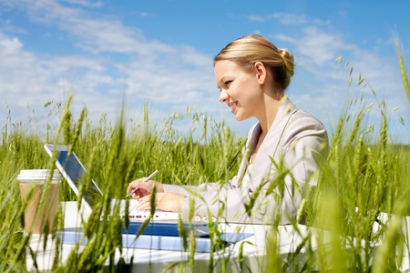 Image of businesswoman in suit sitting in green grass and typing photo