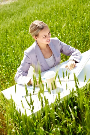Image of businesswoman sitting in green grass and typing photo