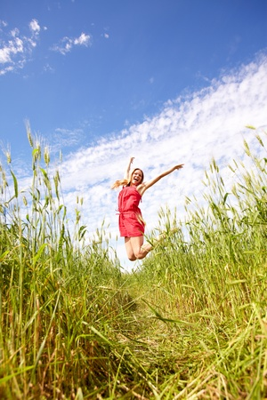 Photo of happy girl leaping over green grass on summer day Stock Photo - 10175281