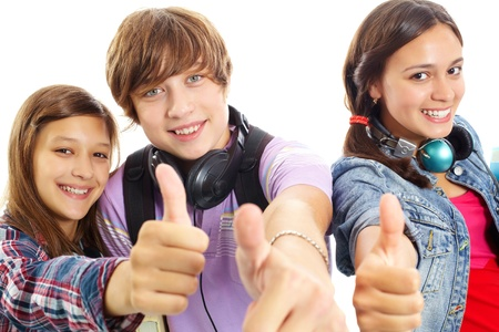 teenage girls: Cute teens with headphones showing thumbs up and smiling at camera