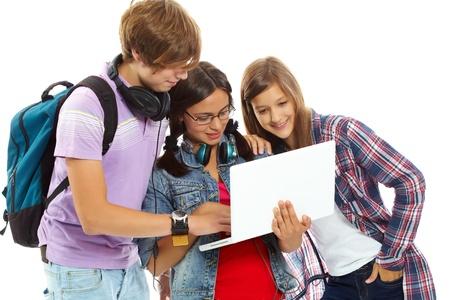 adolescentes estudiando: Tres adolescentes que estudian con portátil Foto de archivo