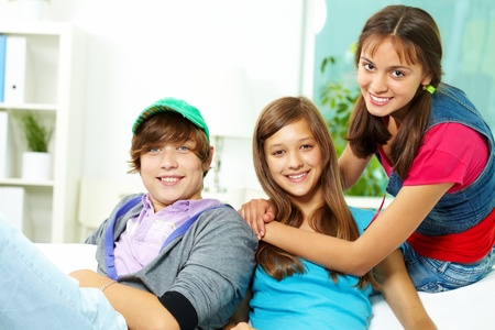 handsome teenage guy: Portrait of three friends sitting together, looking at camera and smiling