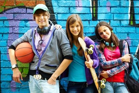 Row of happy Teenager von bemalten Wand sich mit Kamera Standard-Bild