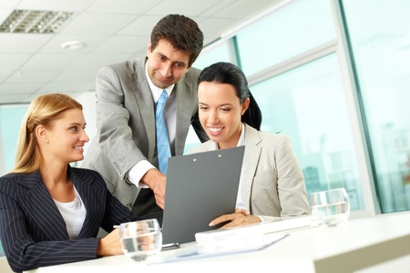 Three business people discussing papers with current results Stock Photo - 10203463