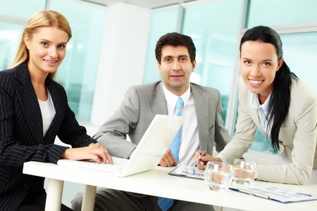 Three business people looking at camera while at workplace  photo