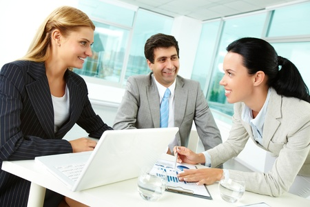 co work: Three business people discussing papers at workplace in office