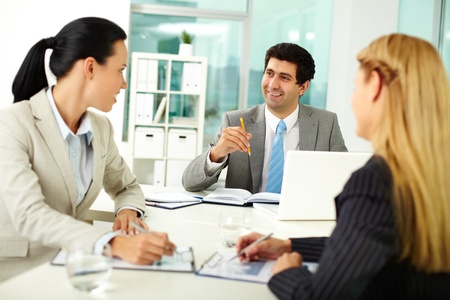 Confident businessman explaining his ideas to colleagues at meeting  photo