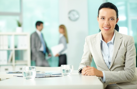 Portrait of a young woman at workplace looking at camera in working environment  photo