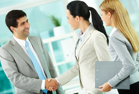 Portrait of successful associates handshaking after striking deal photo