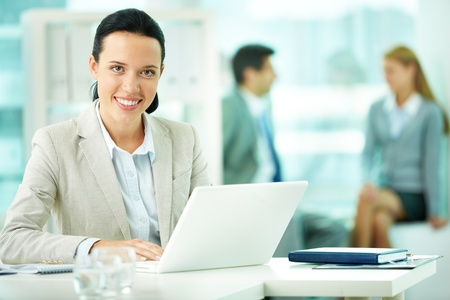 Portrait of pretty secretary working with her partners on background Stock Photo - 10203455