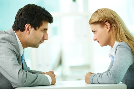 contradiction: Profiles of serious employees looking at each other