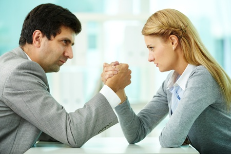 strong arm: Man and woman in arm wrestling gesture on working table during meeting Stock Photo
