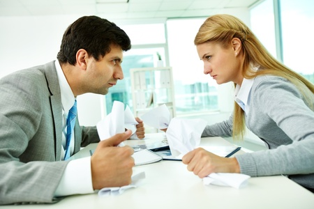 disagreement: Profiles of angry employees with papers looking at each other strictly