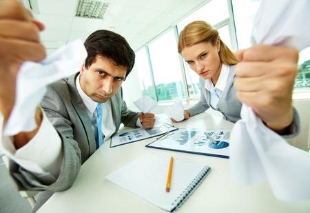 desacuerdo: Retrato de empleados enojados con papeles en las manos mirando a la cámara estrictamente