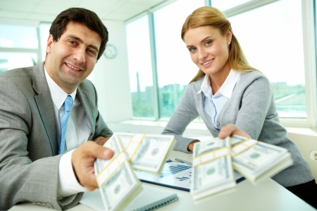 Two business partners at workplace giving money and looking at you Stock Photo