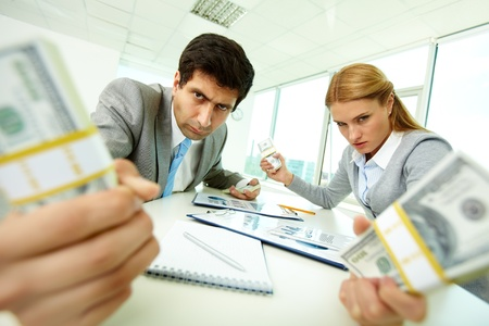 Image of angry employees with dollar bills in hands looking at you with aggression photo