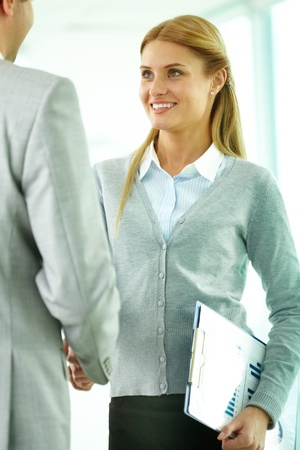 Portrait of happy businesswoman shaking hands with partner at meeting photo