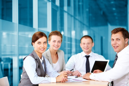 A business team of four sitting at table and looking at camera photo