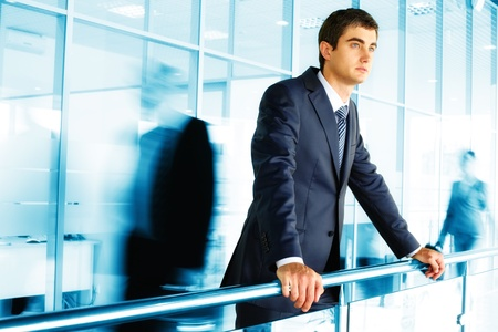 business men: Businessman standing by banisters with walking people on background