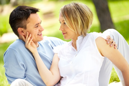 feelings of happiness: Portrait of young amorous couple looking at each other in park Stock Photo
