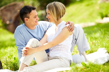 Portrait of young amorous couple looking at each other in park Stock Photo - 10203481