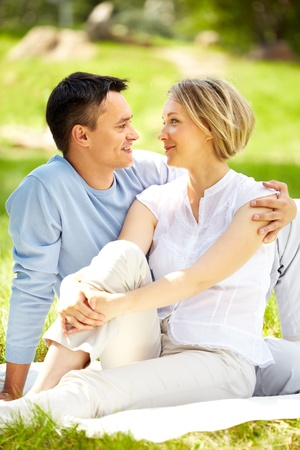 Portrait of young amorous couple having rest in park photo