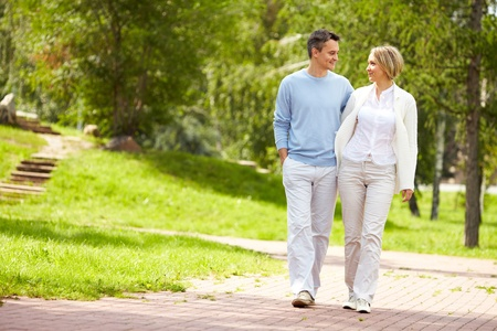 parejas caminando: Retrato de la joven pareja amorosa caminando en el parque en verano Foto de archivo