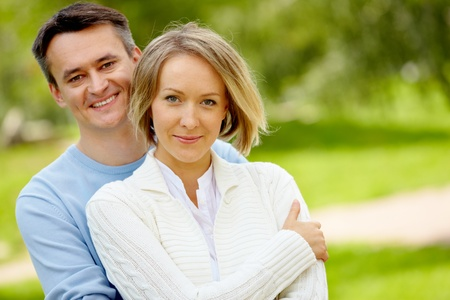 honeymoon couple: Portrait of young happy couple looking at camera outdoors Stock Photo