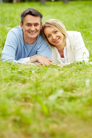 Portrait of young couple looking at camera while having rest in park photo