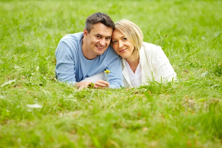 mid adult couples: Portrait of young couple looking at camera while lying on green grass Stock Photo