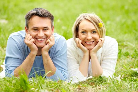 Portrait of happy couple looking at camera while lying on green grass photo