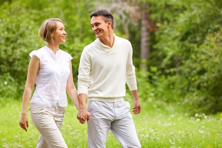 parejas caminando: Retrato de la joven pareja feliz caminando en el Parque de verano Foto de archivo