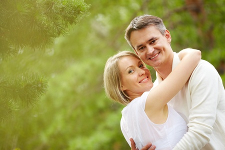 Portrait of happy embracing couple looking at camera photo