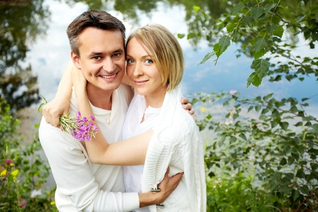 Portrait of happy embracing couple looking at camera in park photo