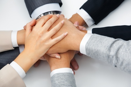joined: Image of business people hands on top of each other symbolizing support and power