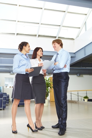 Photo of confident businesspeople standing in the modern office and discussing work   photo