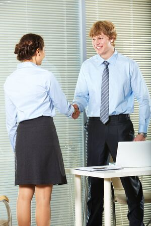 Businesswoman and businessman shaking hands in office photo