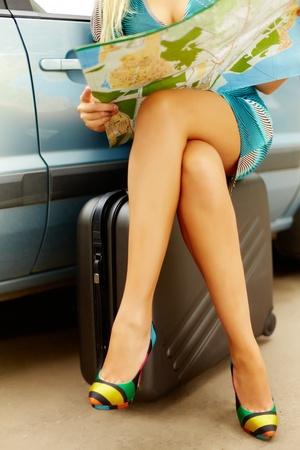 belles jambes: Photo de belles jambes de femme élégante assis sur valise par sa voiture et de chercher emplacement sur la carte