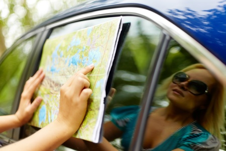 vacation map: Close-up of woman hand pointing at map with her reflection on car window