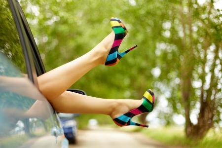 Foto de bonitas piernas de mujer elegante atascado desde la ventana del coche  Foto de archivo