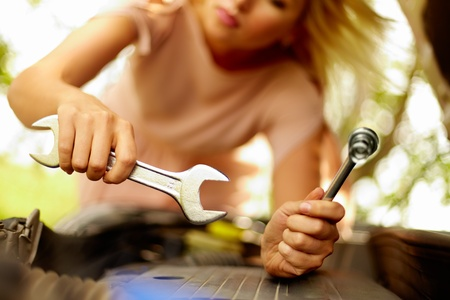 Close-up of female hand with wrench checking engine of car Stock Photo - 10260236