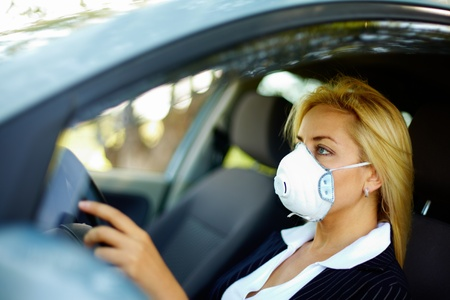 air pollution: Photo of blond female wearing respirator while driving car in polluted area
